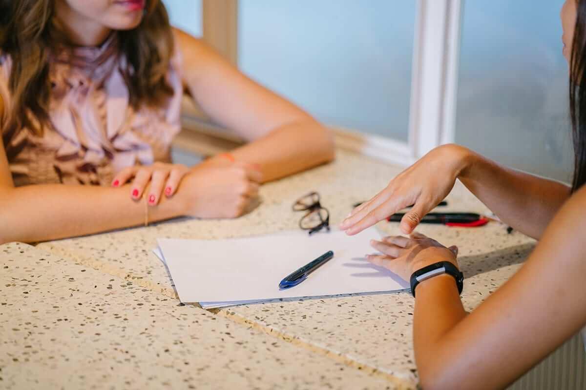 Two women talk during meeting